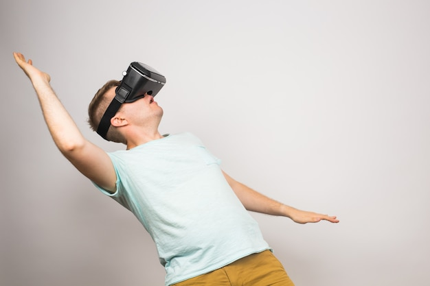 Podekscytowany młody człowiek korzystający z zestawu vr i doświadczający wirtualnej rzeczywistości na szarym tle