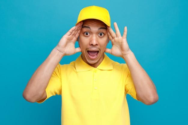 Podekscytowany młody człowiek noszenie munduru i czapkę, trzymając ręce na głowie