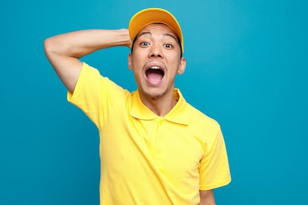 Podekscytowany młody człowiek noszenie munduru i czapkę, trzymając rękę na głowie