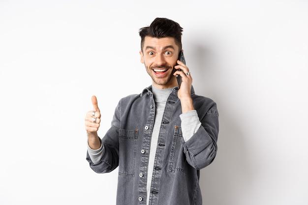 Podekscytowany młody człowiek rozmawia przez telefon i pokazuje kciuki do góry, uśmiechnięty zadowolony, stojąc na białym tle.