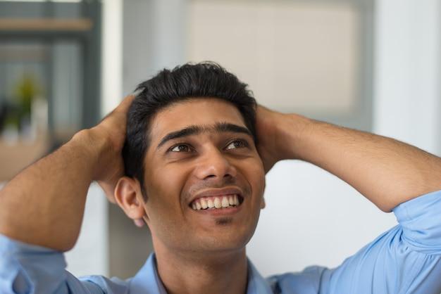 Podekscytowany młody człowiek trzyma głowę w ręce
