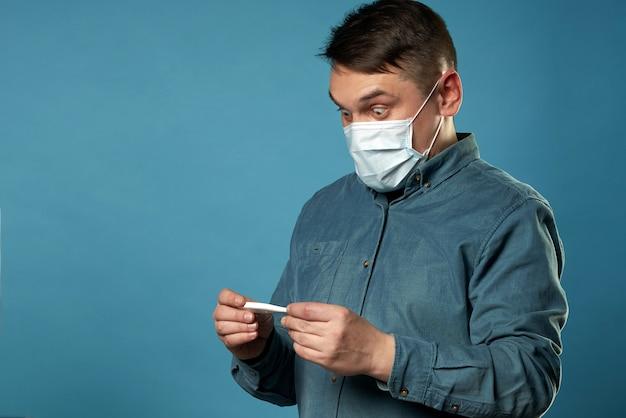 Podekscytowany młody człowiek ubrany w swobodną szmatkę medyczną ochronną