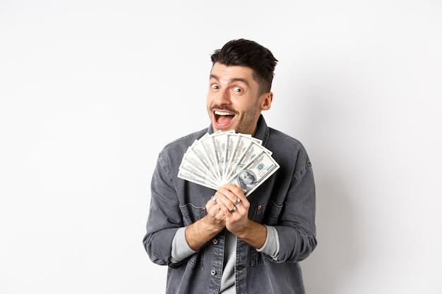 Podekscytowany młody człowiek uśmiecha się i pokazuje dolary, zarabianie pieniędzy, stojąc na białym tle.