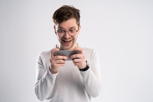 Podekscytowany młody człowiek w biały t-shirt grając w gry na telefon komórkowy na białym tle nad białym tle