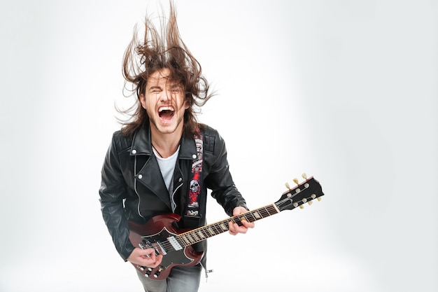 Podekscytowany młody człowiek w czarnej skórzanej kurtce z krzykiem gitary elektrycznej i potrząsaniem głową na białym tle
