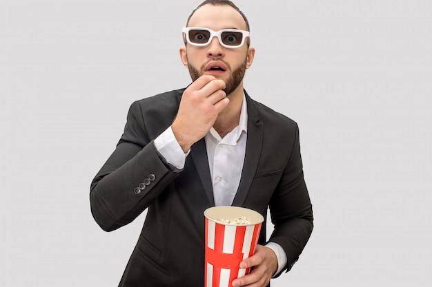 Podekscytowany młody człowiek w garniturze patrzy prosto przed siebie. ma założone okulary do kina. facet je popcorn z małego wiadra.