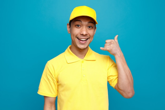 Podekscytowany młody człowiek w mundurze dostawy i czapkę robi gest połączenia