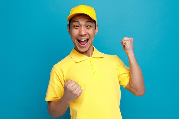 Podekscytowany młody człowiek w mundurze dostawy i czapkę robi gest tak