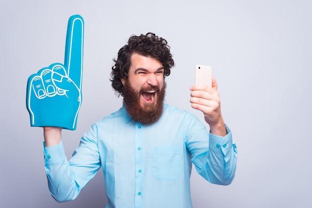 Podekscytowany młody człowiek w rękawiczce wachlarza i trzymający telefon stoi przy szarej ścianie