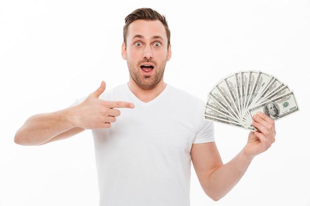 Podekscytowany młody człowiek, wskazując i trzymając pieniądze.