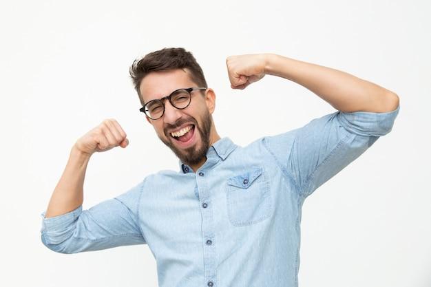 Podekscytowany młody człowiek wyświetlono biceps