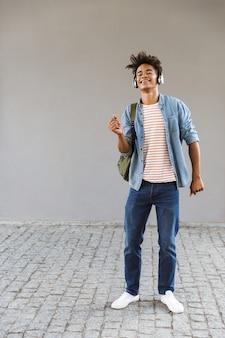 Podekscytowany młody człowiek z plecakiem na zewnątrz