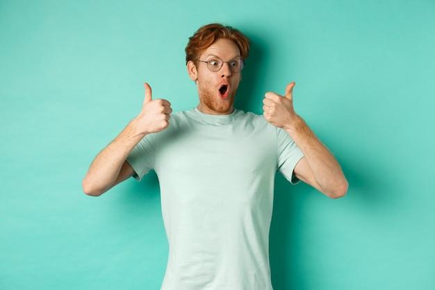 Podekscytowany młody człowiek z rudymi włosami i brodą, z podziwem wpatrujący się w reklamę, pokazujący z aprobatą uniesione kciuki, chwalący ofertę, stojący na turkusowym tle.