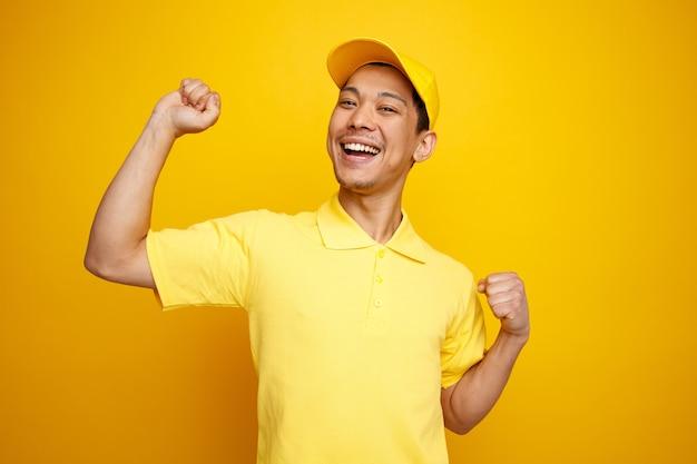Podekscytowany młody doręczyciel w czapce i mundurze, zaciskając pięści do tańca