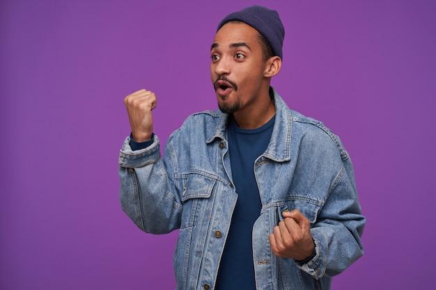 Podekscytowany młody, dość ciemnowłosy brodaty mężczyzna pokazujący pięść, patrząc na bok z poruszoną twarzą, ubrany w niebieską czapkę, sweter i dżinsowy płaszcz, pozując na fioletowej ścianie