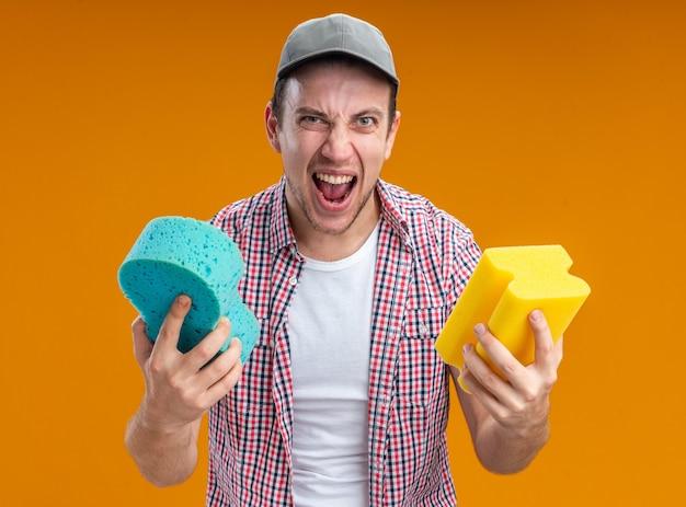 Podekscytowany młody facet sprzątacz w czapce trzymającej gąbki do czyszczenia na białym tle na pomarańczowym tle