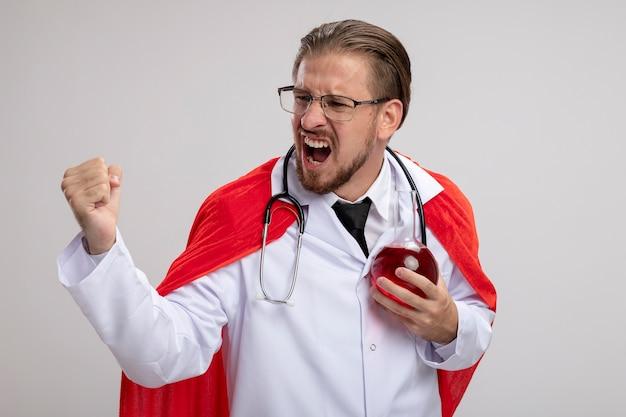 Podekscytowany młody facet superbohatera w szlafroku medycznym ze stetoskopem i okularami, trzymając szklaną butelkę chemii wypełnioną czerwonym płynem, pokazując gest tak na białym tle