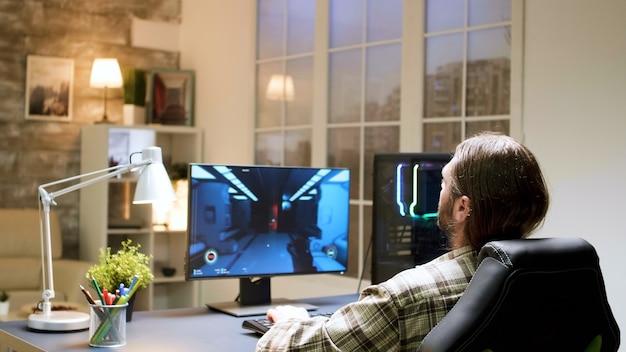 Podekscytowany młody gracz z długimi włosami, siedzący na fotelu do gier. człowiek za pomocą komputera do gier.