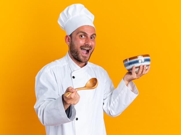 Podekscytowany młody kaukaski kucharz w mundurze szefa kuchni i czapce, patrząc na kamerę trzymającą miskę i łyżkę na białym tle na pomarańczowej ścianie