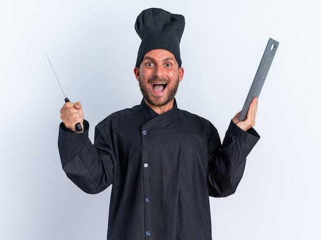 Podekscytowany młody kaukaski kucharz w mundurze szefa kuchni i czapce trzymającej tasak i deskę do krojenia, patrząc na kamerę na białym tle na białej ścianie