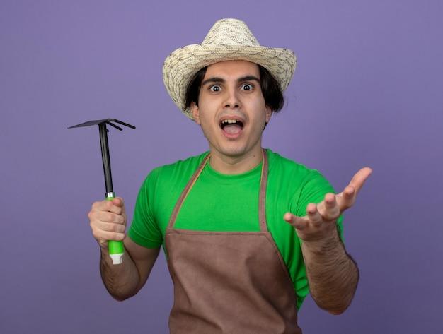 Podekscytowany młody mężczyzna ogrodnik w mundurze na sobie kapelusz ogrodniczy trzymając motyka grabie na białym tle na fioletowo