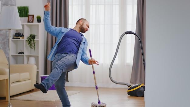 Podekscytowany młody mężczyzna tańczy podczas sprzątania swojego mieszkania