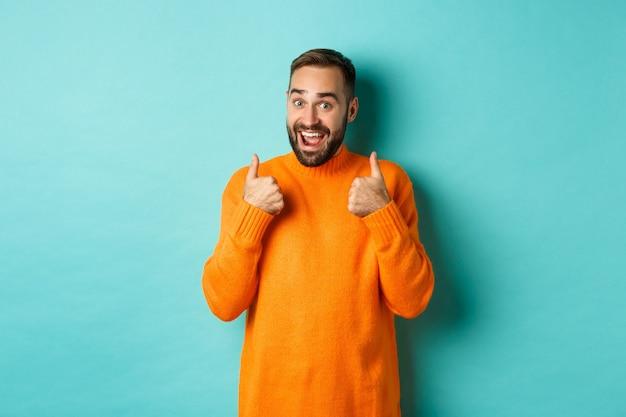 Podekscytowany młody mężczyzna z brodą, pokazujący kciuki w górę z aprobatą, pochwałami lub rekomendacjami, stojący nad jasnoniebieskim tłem