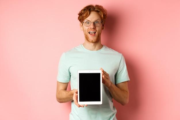 Podekscytowany młody mężczyzna z rudymi włosami i brodą sprawdza promocję online pokazującą pi...