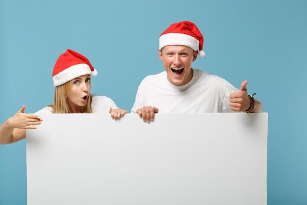 Podekscytowany młody mikołaj para przyjaciół facet i kobieta w świątecznym kapeluszu