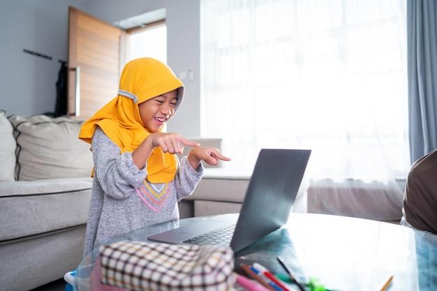 Podekscytowany młody muzułmański dzieciak podczas nauki online w domu przy użyciu laptopa
