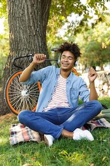 Podekscytowany młody nastolatek z rowerem na zewnątrz