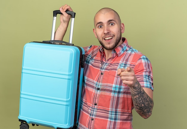 Podekscytowany młody podróżnik kaukaski mężczyzna trzymający walizkę i wskazujący na aparat na białym tle na oliwkowozielonym tle z miejscem na kopię