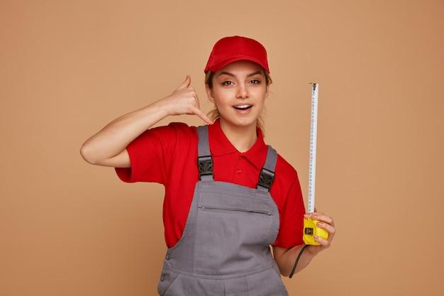 Podekscytowany młody pracownik budowlany kobieta ubrana w czapkę i jednolity trzymając miernik taśmy robi gest połączenia