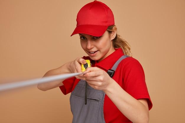Podekscytowany młody pracownik budowlany kobieta ubrana w czapkę i mundur rozciągający się miernik taśmy w kierunku kamery