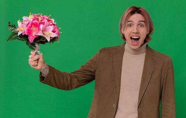 Podekscytowany młody przystojny mężczyzna trzyma bukiet kwiatów