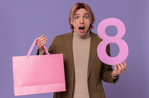 Podekscytowany młody przystojny mężczyzna trzyma różową torbę na prezent i numer osiem