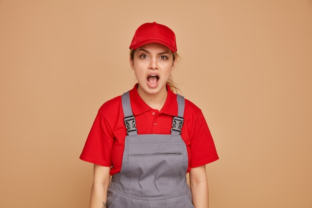 Podekscytowany młody żeński pracownik budowlany na sobie mundur i czapkę