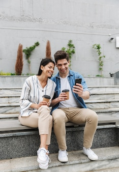 Podekscytowany para mężczyzna i kobieta w zwykłych ubraniach, pijący kawę na wynos i używający smartfona na miejskich schodach na zewnątrz