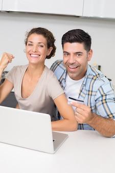 Podekscytowany para razem za pomocą laptopa do sklepu online