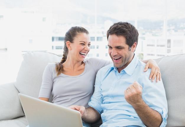 Podekscytowany para siedzi na kanapie za pomocą laptopa ze sobą