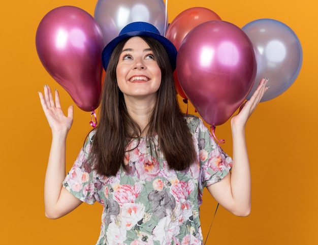 Podekscytowany, patrząc w górę, młoda piękna dziewczyna w kapeluszu stojącym przed balonami rozkładającymi ręce