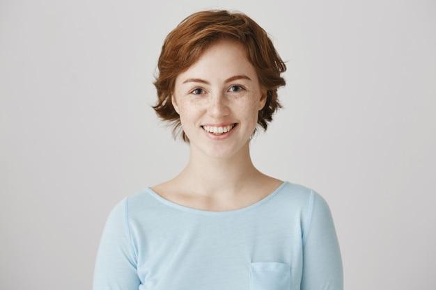 Podekscytowany piękna młoda kobieta uśmiechając się z nadzieją do kamery