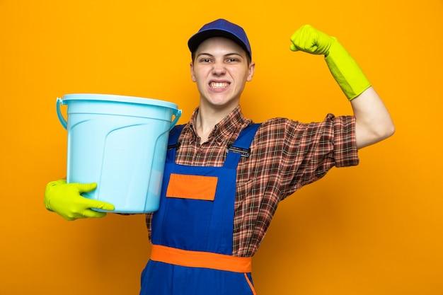 Podekscytowany, pokazując silny gest, młody facet sprzątający ubrany w mundur i czapkę z rękawiczkami, trzymający wiadro