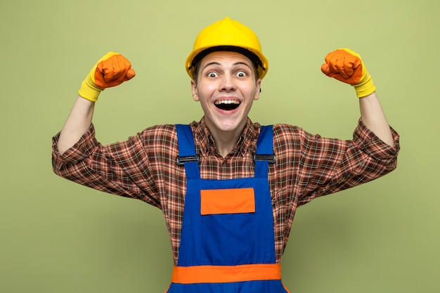 Podekscytowany pokazując silny gest młody mężczyzna budowniczy ubrany w mundur w rękawiczkach