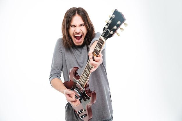 Podekscytowany popularny młody wokalista z długimi włosami krzyczy i gra na gitarze elektrycznej na białym tle