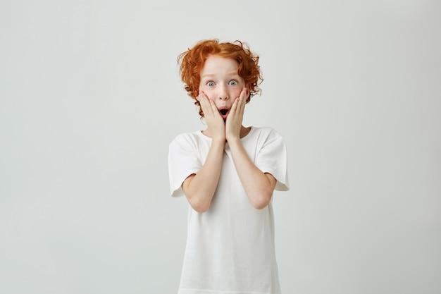 Podekscytowany portret ładny mały rudy chłopiec z piegami w białej koszulce