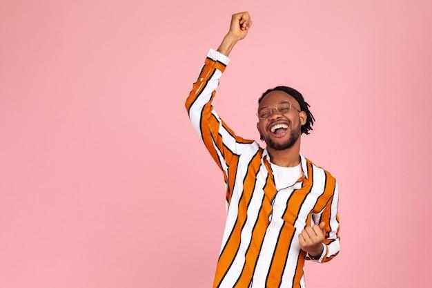 Podekscytowany pozytywny brodaty afroamerykanin tańczący, podnoszący ręce do góry i dobrze się bawiący, dobry nastrój