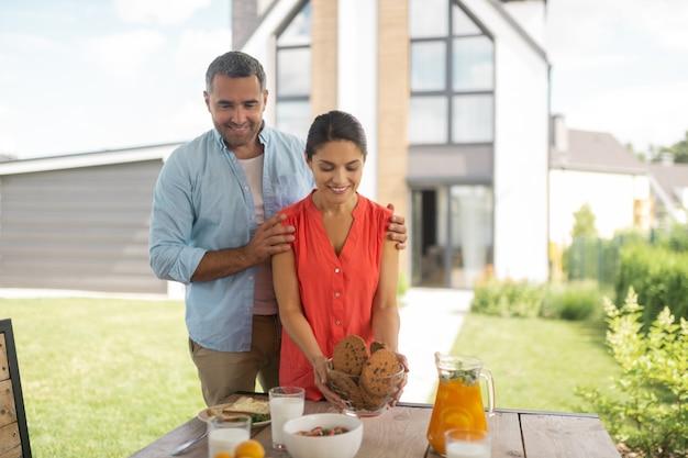 Podekscytowany przed śniadaniem. przystojny brodaty mąż czuje się podekscytowany przed śniadaniem z żoną