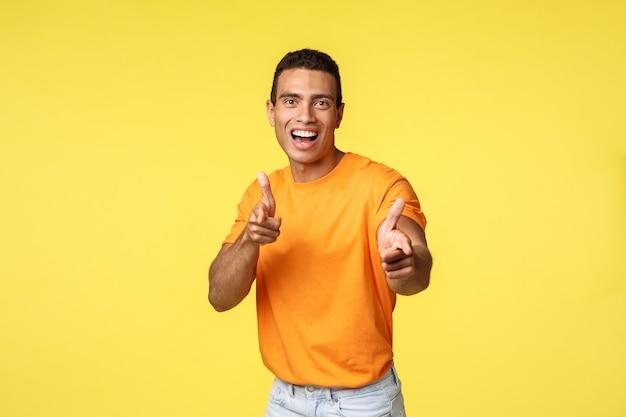 Podekscytowany przyjazny i towarzyski młody przystojny facet w pomarańczowej koszulce