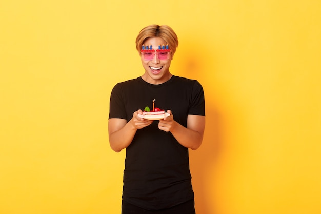 Podekscytowany przystojny azjata w imprezowych okularach, patrząc z nadzieją na tort urodzinowy, jak świętuje urodziny, życzy sobie na zapalonej świecy, stoi żółta ściana